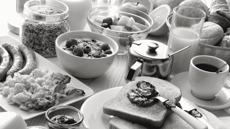 TOEICパート1の例題を紹介するための写真。パンやよーるぐとなどの食べ物が机の上に並べられている様子が映し出されている。この写真の説明として正しいものを次の4つの中から選ぶ。